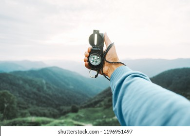 Man explorer searching direction with travel magnetic compass in summer mountains, point of view.