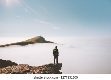 Man explorer standing alone on cliff edge mountain over clouds active travel adventure lifestyle vacations outdoor in Norway