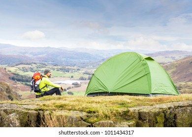 Man explorer with a tent at top of mountain. Young man with a backpack sitting next to his tent at top of hiking trail. Travel and nature concpets