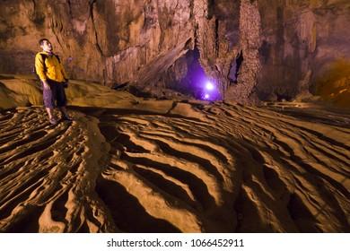 Man exploring beautiful cave at Nguom ngao cave near Ban Gioc waterfalls , Cao bang - North of Vietnam.