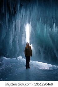 Man exploring ice cave in Baikal Lake, Russia.