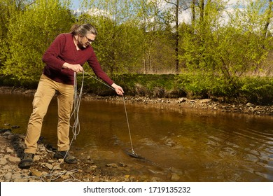 Man exploring river water by magnet on rope