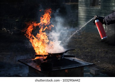 Man extinguishing the fire on an iron pan with foam from a spray can, demonstration during a fire department training, dark background with copy space