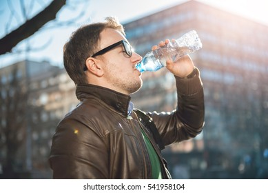 Man with eyeglasses drinking water from plastic bottle in the city