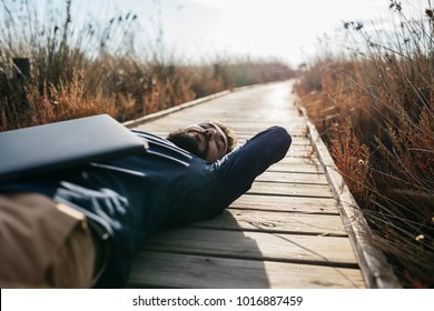 Man with eyes closed lying on wooden pier in sunlight dreaming and lounging alone after work.