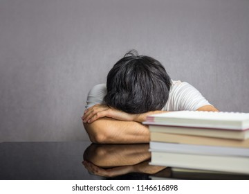 Man face down the table with books