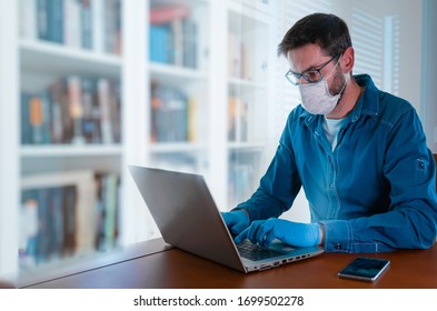 Mann mit Gesichtsmaske und blaue Handschuhe, die von zu Hause aus arbeiten und sich Sorgen um covid-19, Coronavirus, die Aufrechterhaltung der sozialen Distanz und Selbstisolierung.
