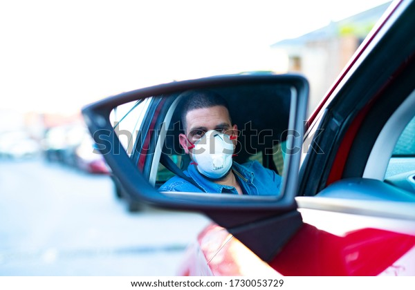 Man with face mask looking at the rear view mirror of the car. Driving with COVID-19 Concept.