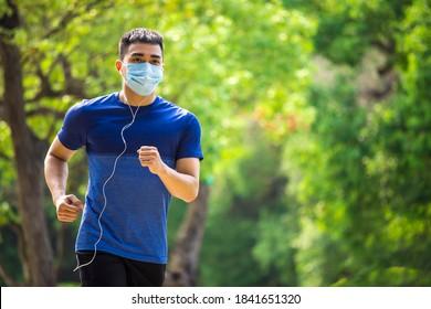 Mann in Gesichtsmaske und Laufen im Park