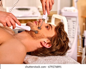 Man facial massage beauty salon. Electric stimulation man skin care . Professional equipment microcurrent lift face. Anti aging rejuvenation non surgical treatment in medical interior room.