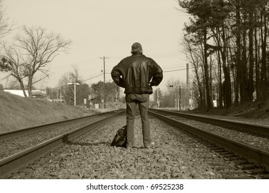 Man facing away, waiting for a train.  Black and white / sepia.