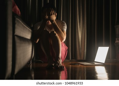 Man facing depression disorder sit on floor with laptop and smartphone beside, conceptual image showing effect from social media resulting in depression disorder