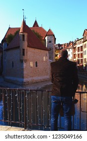 A Man Facing The Medieval Castle And Prison In The Middle Of The Thiou Canal. The Place Is Now A History And Art Museum.