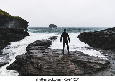 Man facing ocean and waves during a storm. One person standing on the rocks next to the water, looking at the horizon