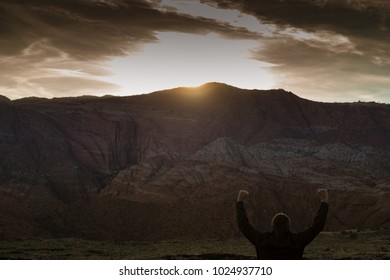 Man facing sunrise in desert with arms raised.