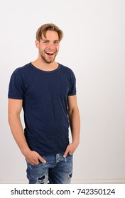 Man with fair hair on white background. Guy in dark blue tshirt and jeans. Macho with smiling face holds hands in pockets. Masculinity and emotions concept