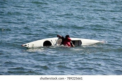 Man fallen into the water trying to get up into his kayak