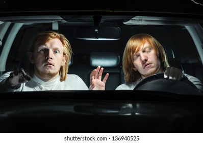 Man falling asleep behind the steering wheel, while his  twin is terrified, trying to warn him of an imminent collision