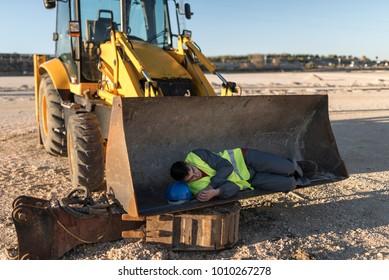 Man for falling asleep on shovel of excavator during work break