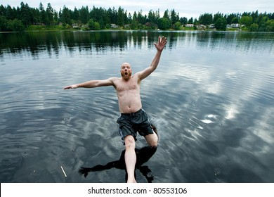 Man falling backwards into a lake.