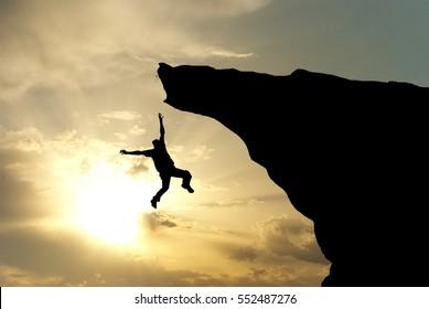 Man falling from the mountain edge. Conceptual scene.