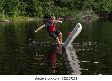 Man falling off stand up paddle board, Muskoka, Ontario, Canada.