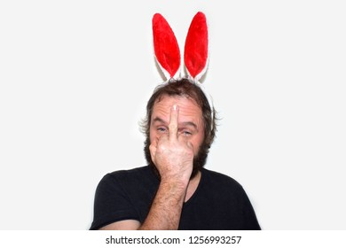 A man with false bunny ears. Bad bunny. Bad Santa.A man in the image of a hare makes faces. Angry hare. Christmas and New Year concept. Isolated on white background. Indecent gesture with your finger.