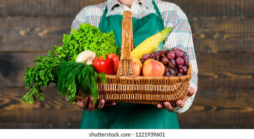 Man farmer presenting eco vegetables wooden background. Fresh organic vegetables in wicker basket. Farmer presenting fresh vegetables. Farmer with homegrown vegetables in basket.