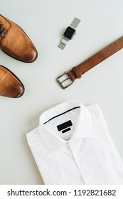 Man fashion composition with watch, shirt, belt and shoes. Flat lay, top view minimal look.