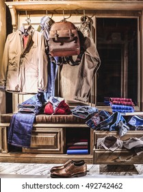 Man fashion stylish classic clothes in home wardrobe. Jacket, jeans, shirt, jumper, shoes, backpack