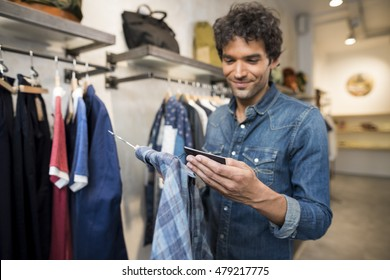 Man in a fashionable shop checking a price tag on shirt.