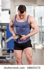 Man fastening his protection belt to lift heavy weights in the gym