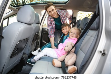 Man fastening security belts on his little children in car