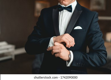 A man fastens cufflink on the white shirt. Close up of a man hand wearing a white shirt and cufflinks.