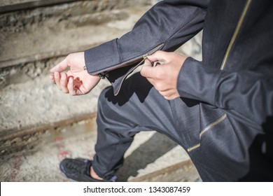 A man fastens his sleeve on a black jacket