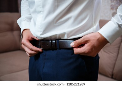 A man fastens a leather belt in his pants