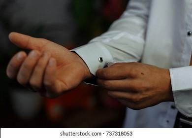 The man fastens the shirt cuffs