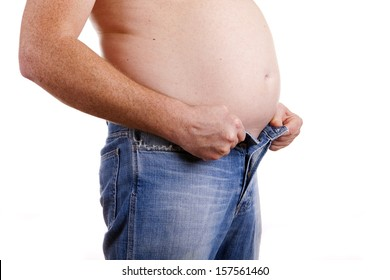 A man with a fat belly struggling to do his jeans up. White background. Concept is to lose weight and lead a healthy lifestyle.
