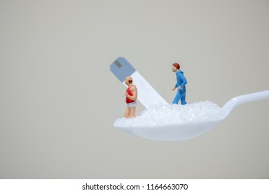 Man and fat oldman miniature figures running on spoon full with sugar and test strip for check blood sugar level. Sport, Fitness, Medicine, diabetes, glycemia, health care and people concept.