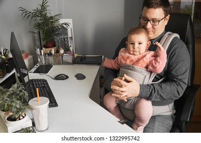 Man father with baby in carrier working at office or home with computer at the desk, parent in office