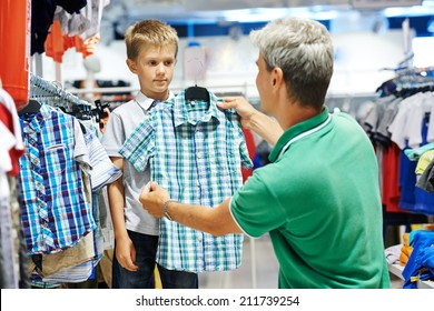 man father choosing shirt with son boy during shopping at garments shop