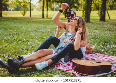Man feeding grapes to his girlfriend and smiling on a picnic