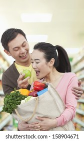 Man feeding woman with apple in grocery store