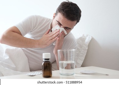 Man feeling cold, lying in the bed and blowing his nose