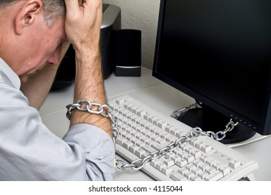 A man feeling as if he is chained to his computer doing a job with no future