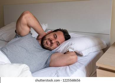 Man feeling neck stiff after sleeping in bed