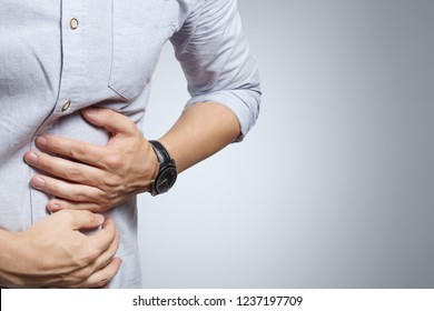 Man feeling terrible stomach ache on grey background
