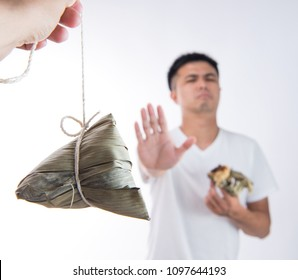A man feels sick after eating too much delicious zongzi(rice dumpling) and saying never eat again on Dragon Boat Festival, Asian traditional food, white background