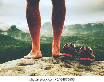 Man feet with hiking shoes on stone mountain background. Spring morning in rocky mountains