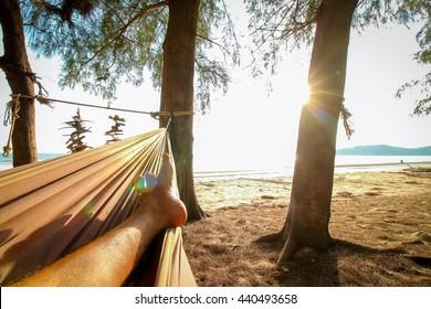 man feet sleeping on swing at the sunset beach background.